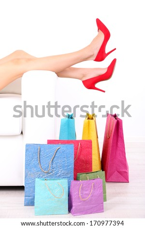 Beautiful female legs in red shoes on sofa with shopping bags on white background