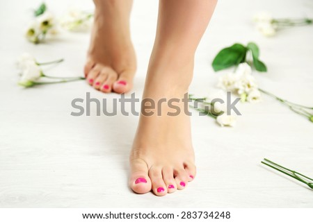 Beautiful female legs on light  floor background - stock photo