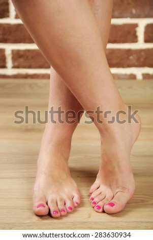 Beautiful female legs on wooden floor background