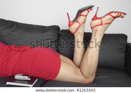 Beautiful female legs wearing red heels and dress relaxing - stock photo