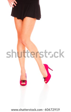 Beautiful female legs wearing red shoes over white background - stock photo