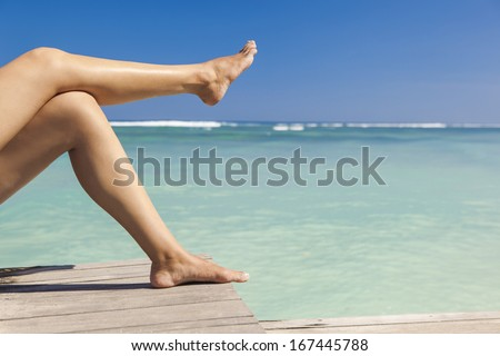 Beautiful female legs with a beautiful tropical beach as background - stock photo