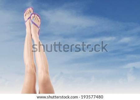 Beautiful female legs with flip-flops upward. Shoot outdoors at summertime - stock photo