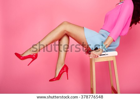 Beautiful female legs with red heels on pink background. Girl in short blue skirt sitting on a bar stool - stock photo