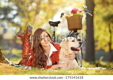 Beautiful female lying on a green grass with a labrador retriever dog in a park - stock photo