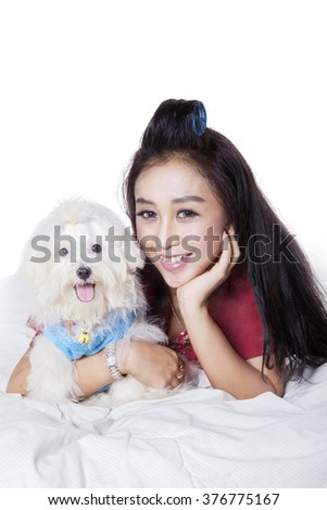 Beautiful female model lying on the bed while hugging a maltese dog and smiling at the camera