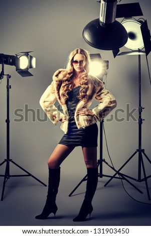 Beautiful female model posing at studio in the light flashes.