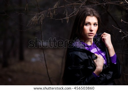 Beautiful female model posing in the dark forest