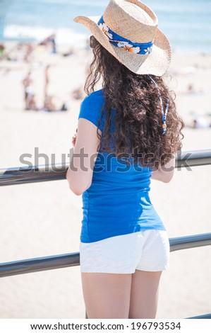 Beautiful female model wearing white shorts and blue shirt on beach pier overlooking beachgoers - stock photo
