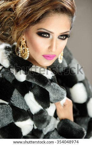Beautiful female model with makeup in a faux fur coat - stock photo