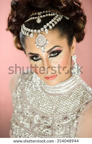Beautiful female model with makeup with jewellery on her head