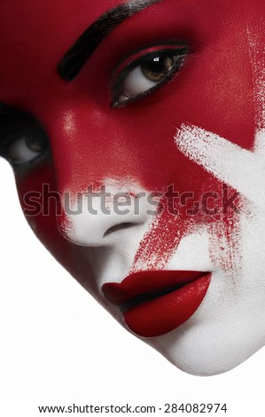 Beautiful female model with white skin, red lips and blood on face. Halloween makeup.