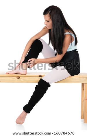 Beautiful female modern jazz contemporary style dancer isolated on a white background. Dancer is wearing a blue leotard, black skirt and leg warmers and is holding her injured ankle. - stock photo