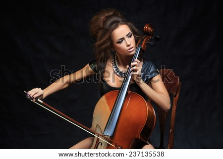 beautiful female musician playing a cello. - stock photo