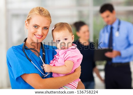 beautiful female nurse holding baby girl in hospital - stock photo
