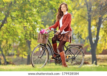 Beautiful female on her bicycle in a park, looking at camera - stock photo