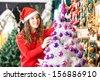 Beautiful female owner in Santa hat decorating Christmas tree at store - stock photo