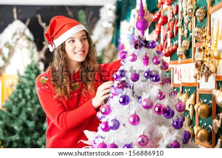 Beautiful female owner in Santa hat decorating Christmas tree at store - stock photo