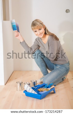 beautiful female painter sitting and smiling on floor
