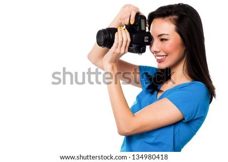Beautiful female photographer taking a snap. Isolated over white background. - stock photo