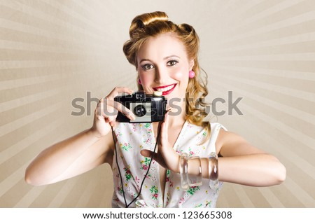 Beautiful Female Pinup Model In Floral Patten Dress Taking A 1950s Happy Snap Photo With Retro Camera - stock photo