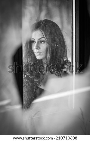 Beautiful female portrait with long hair, sight view. Genuine natural brunette looking away daydreaming, dramatic concept. Attractive woman with beautiful eyes and lips, black and white photo - stock photo
