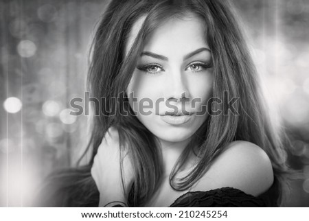 Beautiful female portrait with long hair, studio shot. Genuine natural brunette looking directly to the camera. Attractive woman with beautiful eyes with lights in background, black and white photo - stock photo