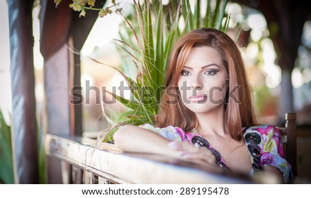 Beautiful female portrait with long red hair outdoor. Genuine natural redhead with bright colored blouse in park. Portrait of a attractive woman with beautiful eyes daydreaming, outdoor shot - stock photo