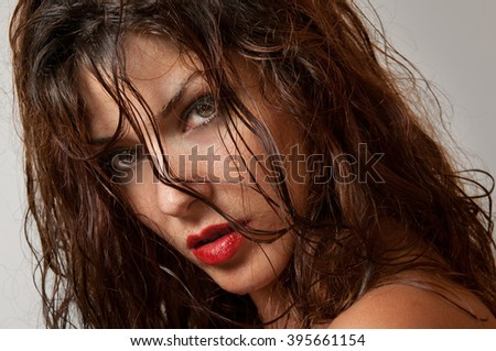 Beautiful female portrait with long wet hair, studio shot. Genuine natural redhead looking directly to the camera after a shower. Attractive woman with beautiful eyes on gray background, side view - stock photo
