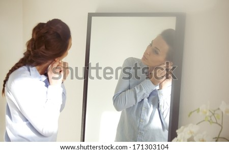 Beautiful female putting on her earring in front of mirror. Businesswoman getting dressed for work. Caucasian female model in blue shirt. - stock photo