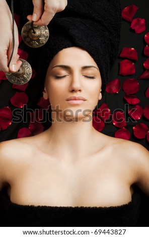 Beautiful female receiving energy sound massage in spa, eyes closed - stock photo