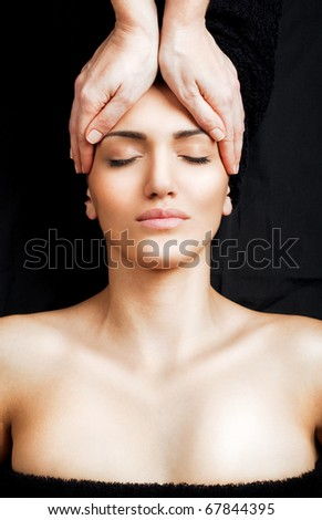 Beautiful female receiving relaxing facial massage at spa, eyes closed - stock photo