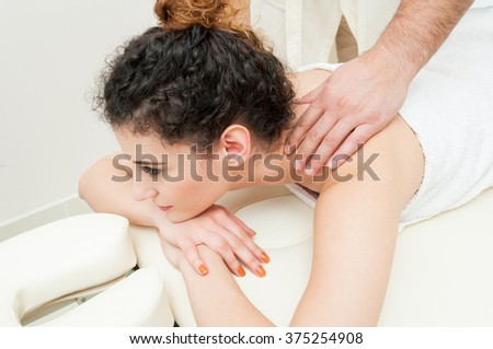 Beautiful female resting in beauty salon and getting spa massage by male masseur - stock photo