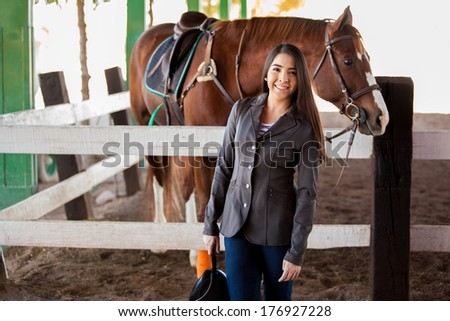 Beautiful female rider standing next to her horse at the track and smiling - stock photo