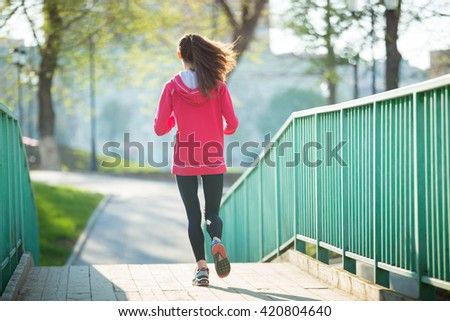 Beautiful female running on the bridge during everyday practice. Fitness woman jogging outdoors in park and moving away from camera. Sport active lifestyle concept. Full length. Back view - stock photo