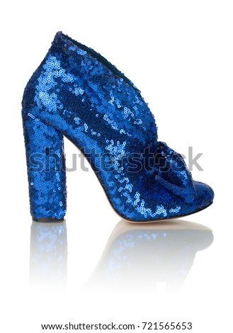 Beautiful female shiny luxury blue shoe decorated with a bow on high heel on a white background, side view