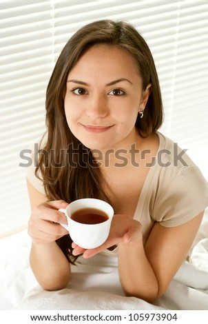 Beautiful female sitting on a bed with a cup on a light background - stock photo