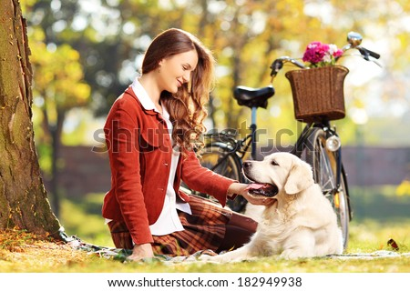 Beautiful female sitting on a green grass and looking at her labrador retriever dog in a park - stock photo