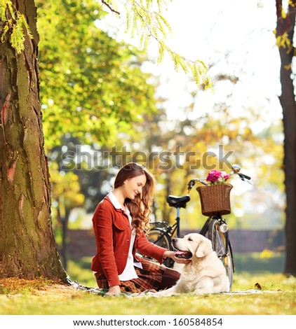 Beautiful female sitting on a green grass and looking at her labrador retriever dog in a park, shot with a tilt and shift lens - stock photo