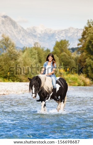 Beautiful Female sitting on horse while crossing river in a mountainous landscape