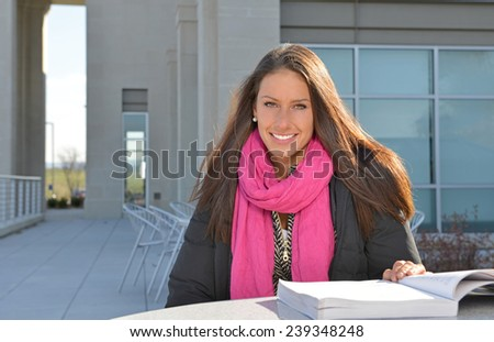 Beautiful female student (brunette) sitting outside in late fall or winter studying - stock photo