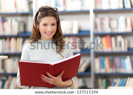 Beautiful female student in a library  - stock photo