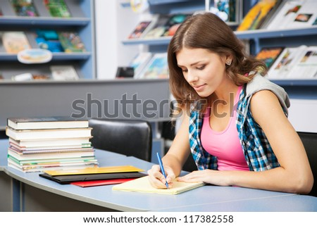 Beautiful female student in a university library - stock photo