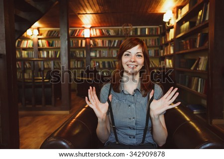 Beautiful female student in a university library having fun