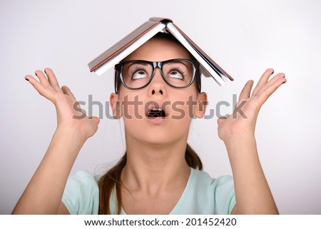 Beautiful female student in glasses cover her head with book - stock photo