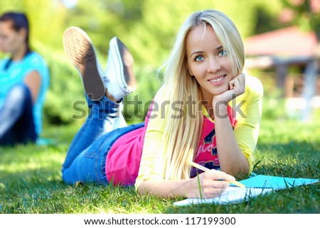 beautiful female student lies on green lawn and learns - stock photo