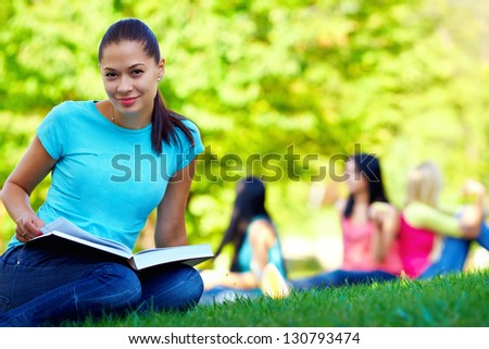 beautiful female student on green lawn - stock photo