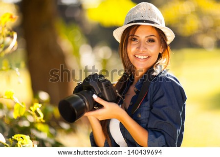 beautiful female student photographer with her camera at the park - stock photo