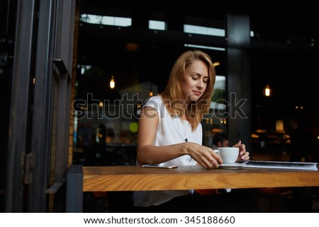 Beautiful female student relaxing in cafe after her lectures in University, charming hipster girl waiting for her friends in coffee shop, attractive woman thinking about something while sitting in bar - stock photo