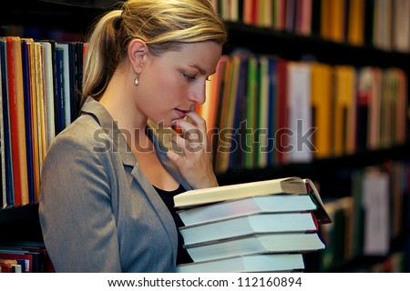 Beautiful female student standing in a library deeply immersed in a book wth her finger to her lip in thought - stock photo